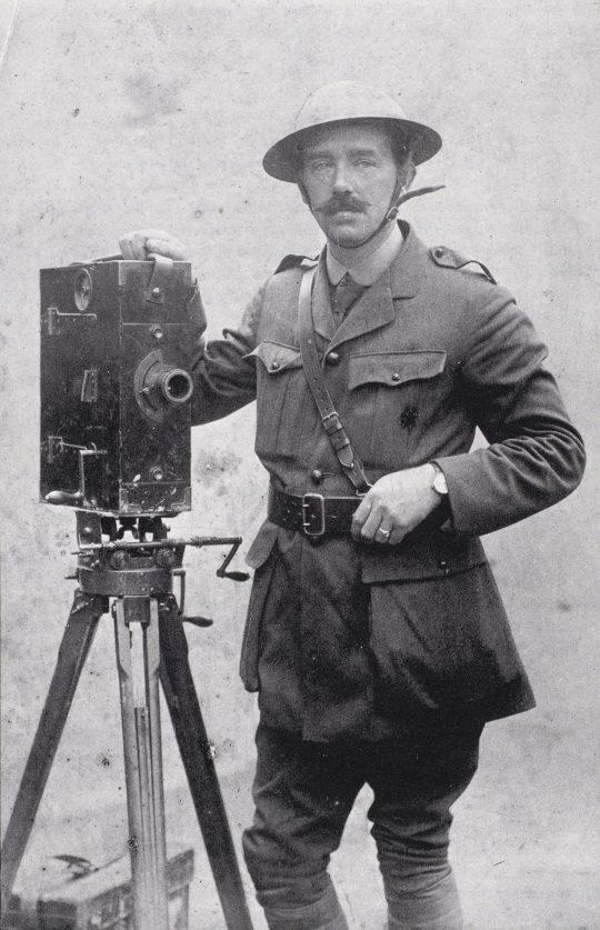J. P. McDowell, en av Storbritanniens mest kända filmfotografer under första världskriget, bredvid en mekanisk filmkamera av märket Moy & Bastie.