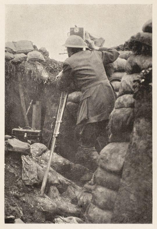 G. H. Malins i aktion under slaget vid Somme 1916. Sandsäcken till höger ska dölja handens vevrörelser (rörelse drar till sig uppmärksamhet, vilket var förenat med livsfara i dessa sammanhang). Ur G. H. Malins, How I Filmed the War (1920).