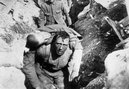 Ikonisk filmbild från första världskriget som visar hur brittisk soldat kastar en hastig blick mot kameran när han för sårad kamrat i säkerhet. (slaget vid Somme, 1916)